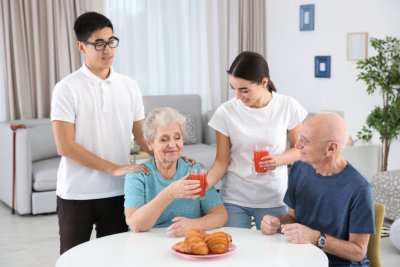 two caregiver assisting the old couple on their meal